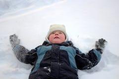 Chłopiec lying on the beach w śniegu Zdjęcia Stock