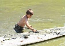 Chłopiec mąci surfboard w wodzie Zdjęcia Royalty Free