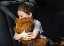 Chłopiec męcząca i śpi uściśnięcie teddybear w samochodzie Zdjęcia Royalty Free