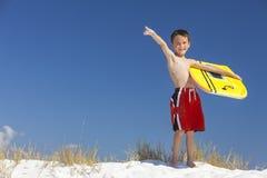 Chłopiec Męski dziecko Wskazuje na plaży Z Surfboard Obrazy Royalty Free