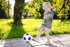Chłopiec ma zabawę bawić się mecz piłkarskiego na pogodnym letnim dniu Fotografia Royalty Free