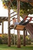 Chłopiec ma zabawę na huśtawce Zmierzch w parku Zdjęcia Stock