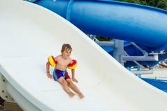 Chłopiec ma zabawę na waterslide basenie Fotografia Royalty Free