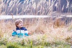Chłopiec ma zabawę z sitowiem blisko lasowego jeziora Obraz Stock