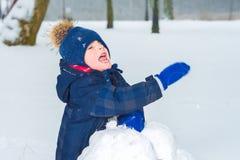 Chłopiec macha jego rękę w śniegu Dziecko bawić się obrazy royalty free