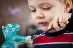 Chłopiec maluje ceramiczną postać Obrazy Royalty Free