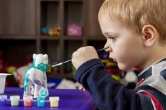 Chłopiec maluje ceramiczną postać Zdjęcie Stock