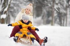 Chłopiec, matka, babcia i niania ono ślizga się w parku podczas opadu śniegu/ obraz stock