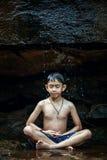 Chłopiec medytuje pod siklawą kołysa w drewnach gdzieś Zdjęcia Stock