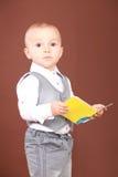 Chłopiec mienie i pozycja książka w jego wręcza Obraz Stock