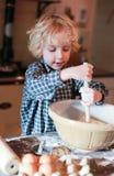 Chłopiec miesza mąkę w pucharze Zdjęcie Royalty Free