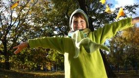 Chłopiec miotania jesieni liście na pogodnym parku zdjęcie wideo