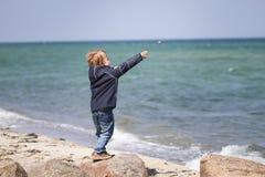 Chłopiec miotania kamienie przy plażą zdjęcia stock