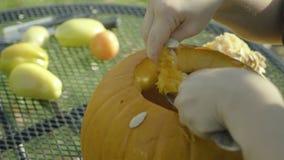 Chłopiec muska spoonful Halloweenową przerażającą głowę Dziecko ręki rzeźbią Halloween bani strach na wróble zbiory