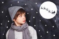Chłopiec myśleć o boże narodzenie nocy; fotografia royalty free