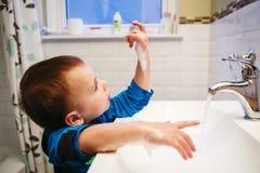 Chłopiec myje jego ręki fotografia royalty free