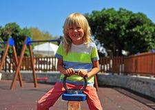 Chłopiec na huśtawce przy dzieciaka ` s boiskiem obrazy stock