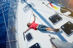 Chłopiec na pokładzie żeglowanie jachtu na lato rejsie Podróżuje przygodę, jachting z dzieckiem na rodzinnym wakacje Zdjęcie Royalty Free