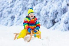 Chłopiec na sanie przejażdżce Dziecka sledding Dzieciak na saneczki fotografia stock