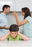 Chłopiec nakrywkowi ucho podczas gdy rodzice kłóci się w kuchni Zdjęcie Royalty Free
