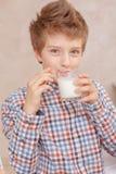 Chłopiec napoje mleko i uśmiechy Zdjęcie Royalty Free