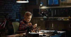 Chłopiec naprawia zabawkarskiego samochód zbiory wideo