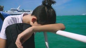 Chłopiec nastolatek cierpi od ruch choroby podczas gdy na łódkowatej wycieczce Strach podróżować podczas a lub choroba wirus fotografia royalty free