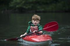 Chłopiec nastolatek kieruje kajakowego kajaka na szerokiej rzece zdjęcia stock
