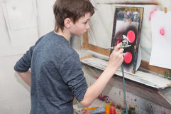 Chłopiec nastolatek maluje z airbrush jaskrawy barwiącymi obrazkami w artistical studiu 24, 2016 - Rosja Moskwa, Styczeń, - Zdjęcia Royalty Free