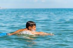 chłopiec nastolatek pływa w morzu Zdjęcia Stock