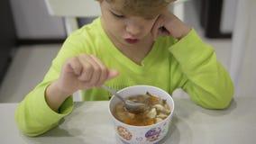 Chłopiec niechętnie je polewkę przy stołem zdjęcie wideo