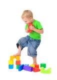 Chłopiec niszczy zabawkarskiego budynek zdjęcia royalty free