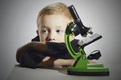 Chłopiec no no studiuje smutno kochanie Uczniowski działanie z mikroskopem mądry chłopak Edukacja Fotografia Stock