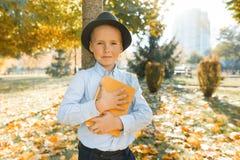 Chłopiec obejmująca ukochany książka i faworyt Tło jesieni pogodny park, złota godzina obraz stock