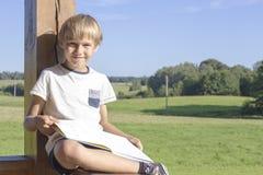 Chłopiec obsiadanie i czytelnicza książka przy latem tarasujemy Przypadkowi ubrania w kontekście niebieskie chmury odpowiadają tr Fotografia Stock