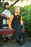 Chłopiec obsiadanie na ławce i dziewczynie w pięknej sukni Obrazy Royalty Free