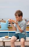 Chłopiec obsiadanie na ławki łasowania pizzy obraz royalty free