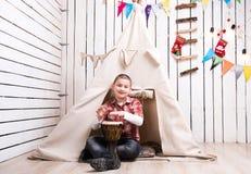 Chłopiec obsiadanie na bawić się blisko wigwamu bębenie i podłoga Zdjęcia Royalty Free