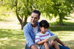 Chłopiec obsiadanie na jego ojcuje podołek i używać cyfrową pastylkę w parku zdjęcie royalty free
