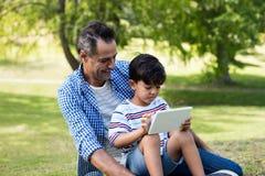 Chłopiec obsiadanie na jego ojcuje podołek i używać cyfrową pastylkę w parku zdjęcie stock