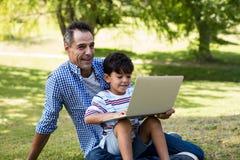 Chłopiec obsiadanie na jego ojcuje podołek i używać laptop w parku fotografia stock
