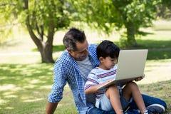 Chłopiec obsiadanie na jego ojcuje podołek i używać laptop w parku zdjęcia stock