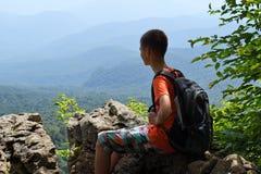 Chłopiec obsiadanie na krawędzi faleza z plecakiem zdjęcie royalty free