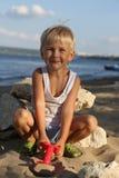 Chłopiec obsiadanie na piasku na plaży blisko rzeki Obraz Stock