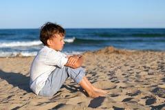 Chłopiec obsiadanie na piasku przy plażą Zdjęcia Royalty Free