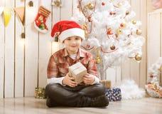 Chłopiec obsiadanie na podłogowym pobliskim nowego roku drzewie Obrazy Stock