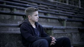 Chłopiec obsiadanie na stadium trybunie, zniszczeniu i ubóstwie wokoło, miasto po wojny zdjęcie stock
