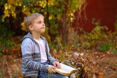 Chłopiec obsiadanie w drewnach na beli obraz stock