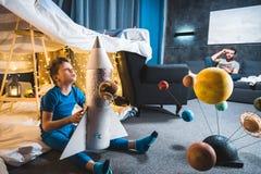 Chłopiec obsiadanie w powszechnym forcie z zabawki rakietą i układ słoneczny modelujemy Zdjęcie Royalty Free