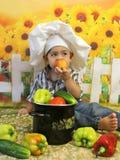 Chłopiec obsiadanie w szefa kuchni kapeluszu z warzywami je brzoskwinię obrazy stock